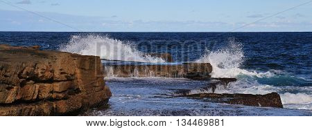Scene at the coast of Sydney. Rocks and splashing Pacific waves.