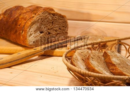 marble sliced wheat - rye bread on a wooden board with a straw basket and slices of bread in it