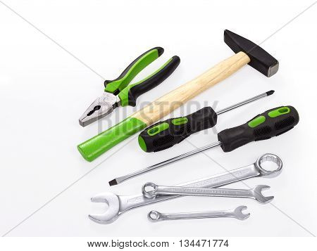 The hammer, spanner, pliers and screwdrivers on a white background. Hammer with wood handle. The back end handle paited in green color. Screwdriver and pliers with grenn piece