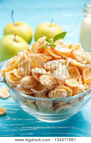 Healthy breakfast with cornflakes green apple milk on the turquoise blue wooden background.