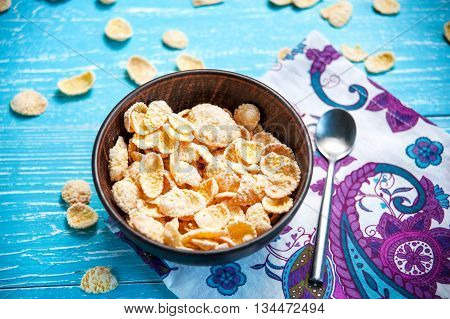 cornflake cereal in bowl with spoon on table with napkin closeup