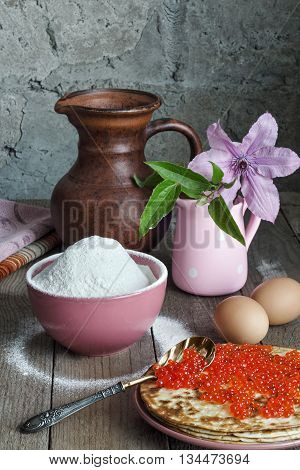 Pancakes with red caviar on a plate. Antique caviar spoon. In a bowl, flour, and eggs on a grey background and rough wooden surface. A pitcher and a vase with flowers in the background.