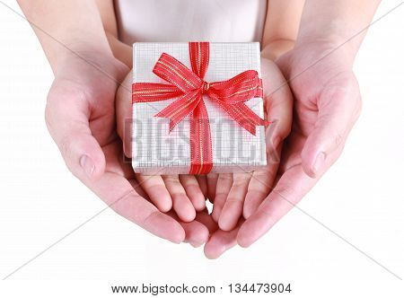 Hands holding beautiful gift box, adult and child giving gift, Christmas holidays and greeting season concept
