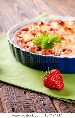 Single Harvested Strawberry In Front Of Fruit Pie In Blue Bowl On Green Towel