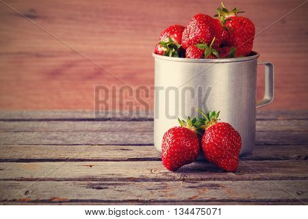 Vintage Retro Photo Of Two Strawberries In Front Of Aluminum Cup