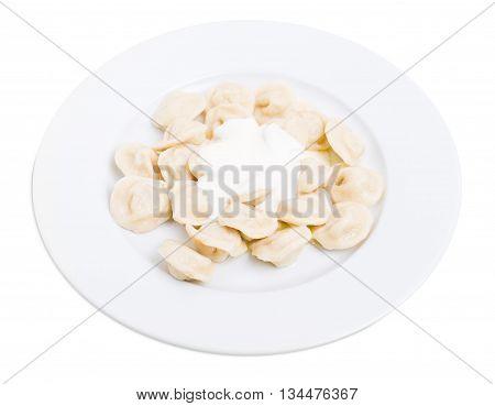 Russian pork dumplings pelmeni with fresh sour cream. Isolated on a white background.