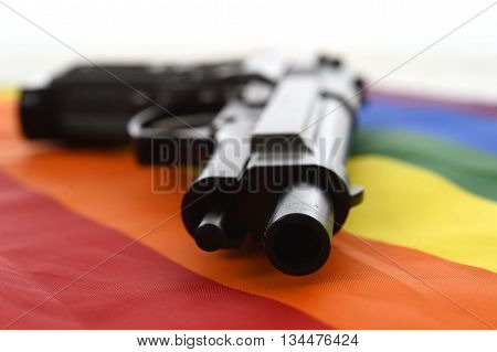 still life with close up gun resting on gay parade flag representing sexual discrimination and intolerance and attack to human rights and sexual freedom