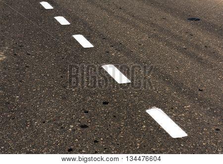 White Road Line On Dirty Asphalt Texture.