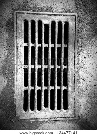 Black and white sewer drain on the road