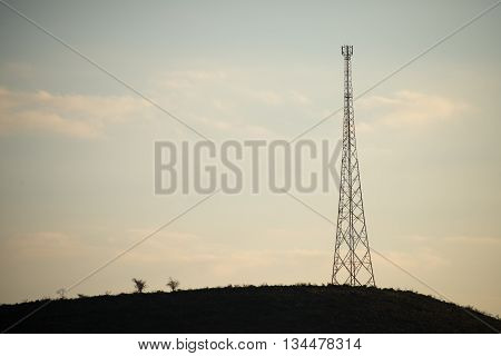 A mobile phone tower stand on a hill in the distance.
