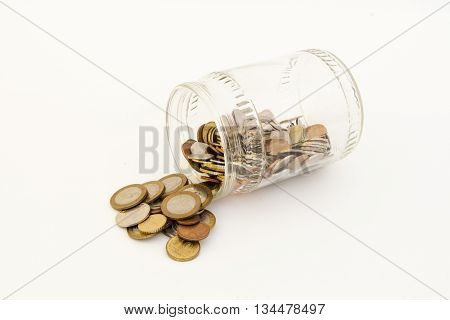 Transparent bank with coins of different metals of different denominations from different countries