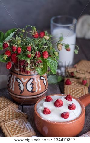 Strawberry with cream in a ceramic Cup, cookies and milk in glass on old wooden surface. Bouquet with strawberries in a ceramic vase. In a rustic style.