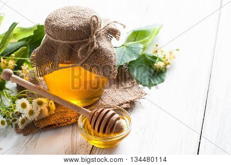 Natural linden honey. Honey in glass jar and dipper on white background with flowers.