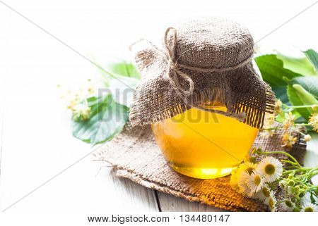 Natural linden honey. Honey in glass jar on white background with flowers.