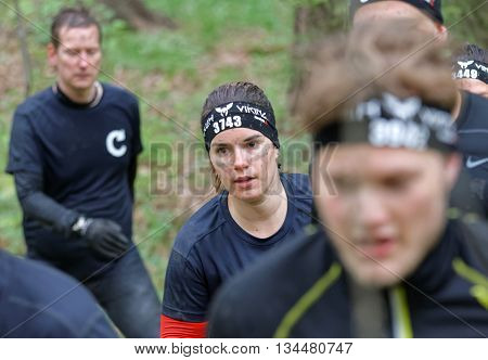 STOCKHOLM SWEDEN - MAY 14 2016: Group of men and women running only one woman in focus in the obstacle race Tough Viking Event in Sweden May 14 2016