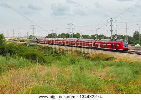 Red israeli passenger train in motion out of the city near Highway 4.