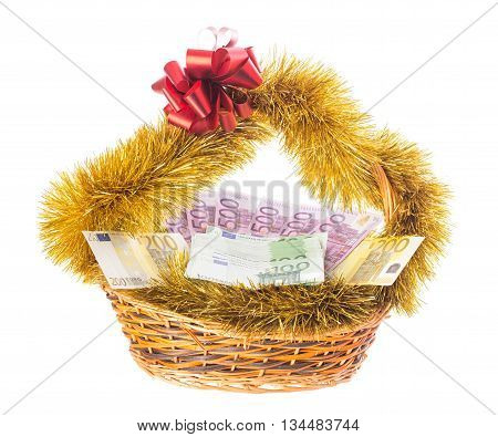 Wicker basket full of euro bills with christmas golden tinsel and red ribbon. Isolated on a white background.