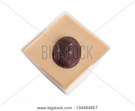 Delicious milk chocolate dessert with dark chocolate portrait candy on top. Macro. Isolated on a white background.