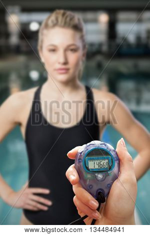 Close up of a hand holding a timer on a white background against fit woman with hands on hips