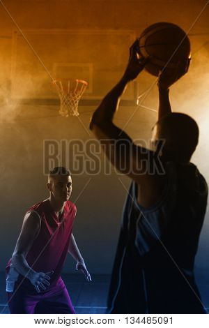 Portrait of two men playing basketball on a gym