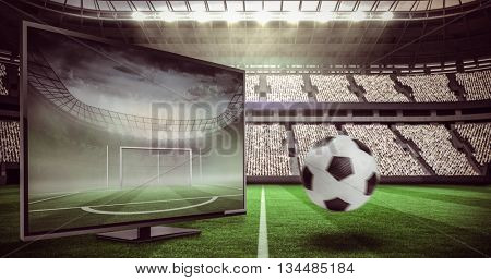 Black and white leather football against football pitch in large stadium
