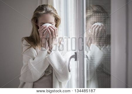 Attractive woman drinking morning coffee by the window