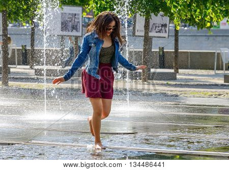MOSCOW, RUSSIA - May 26, 2016: Unknown beautiful girl bathing in city fountain. Hot summer heat. Girls in wet jeans blouse and skirt. Icy freshness, happiness.