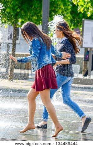MOSCOW, RUSSIA - May 26, 2016: Two unknown girl bathing in city fountain. Hot summer heat. Girls in wet jeans, skirt and blouse. Bright emotions on face. Icy freshness, happiness.