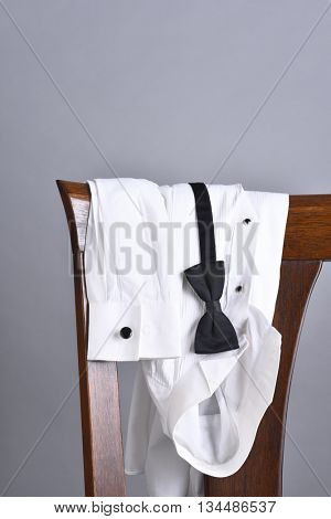 Closeup of a tuxedo shirt draped over a chair back with a black bow tie. Vertical format with copy space.