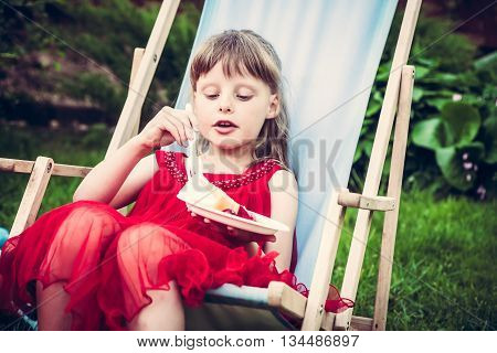 young mannered fashion girl in red dress relaxing in chaise lounge eat cake during outdoor party in the garden