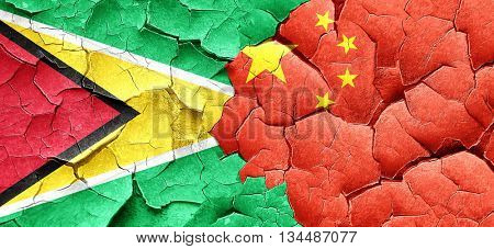 Guyana flag with China flag on a grunge cracked wall