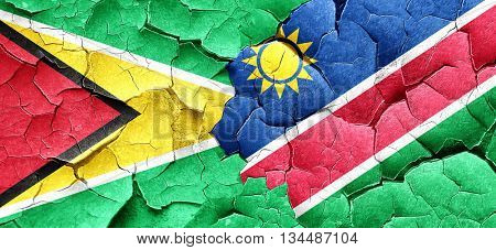 Guyana flag with Namibia flag on a grunge cracked wall