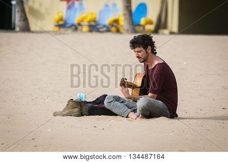 SANTA CRUZ, TENERIFE, SPAIN - DECEMBER 8, 2015: Street musician with a guitar sitting at sandy beach of Tenerife island, Spain