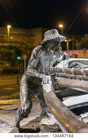 SANTA CRUZ, TENERIFE, SPAIN - DECEMBER 8, 2015: Sculpture of old fisherman with boat at Santa Cruz town on Tenerife island, Spain