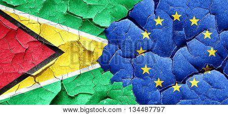 Guyana flag with european union flag on a grunge cracked wall