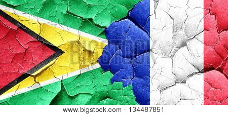 Guyana flag with France flag on a grunge cracked wall