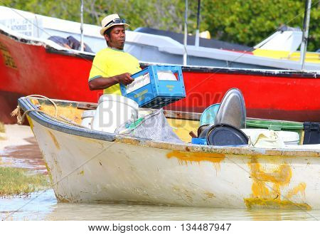ILE AUX CERFS, MAURITIUS ISLAND - OCTOBER 31, 2015 : Unidentified creole sailors loading boats. Local shipping among isles near Mauritus. Native people working in Africa.