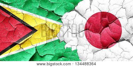 Guyana flag with Japan flag on a grunge cracked wall