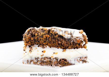Delicious poppy seed cake with walnuts. Macro. Located against black background.