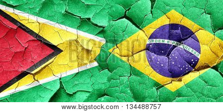 Guyana flag with Brazil flag on a grunge cracked wall