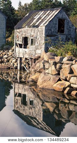 Dilapidated old wooden shack reflecting in the water
