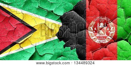 Guyana flag with afghanistan flag on a grunge cracked wall