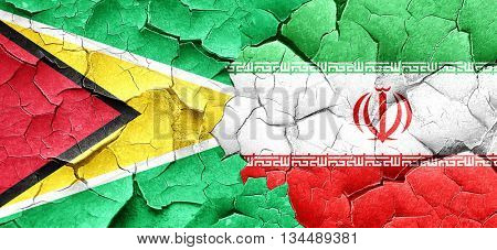 Guyana flag with Iran flag on a grunge cracked wall