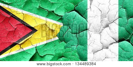 Guyana flag with Nigeria flag on a grunge cracked wall