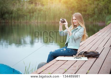 Outdoor summer smiling lifestyle portrait of pretty young woman traveling with camera and making pictures. Young girl tourist making photo