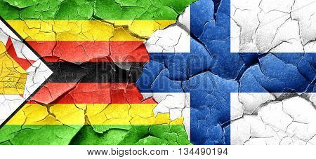 Zimbabwe flag with Finland flag on a grunge cracked wall