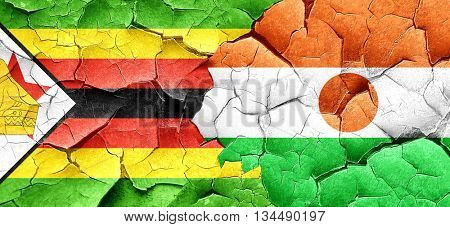 Zimbabwe flag with Niger flag on a grunge cracked wall