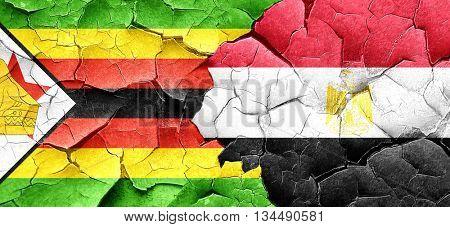 Zimbabwe flag with egypt flag on a grunge cracked wall