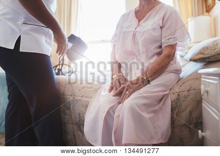 Cropped shot of home caregiver with senior woman sitting on bed. Female doctor visiting her senior patient at home.