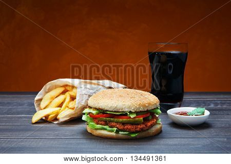 Fast food. Hamburger, potato wedges, cola drink. Takeaway food. Wrapped slices wedges, packaging, Cola glass, tomato sauce, double cheese hamburger at rustic wood and red background.